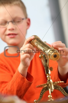 Boy is looking through a classic telescope.