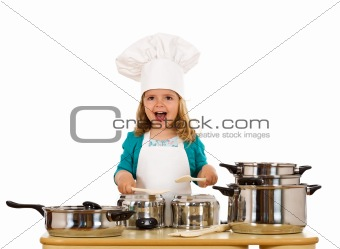 Happy little girl with chef hat making noise with the cooking po