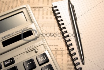 Calculator, pen, notebook and newspaper. Financial concept.