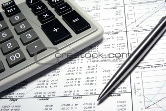 Calculator, steel pen and financial data with graphs.