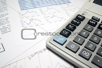 Calculator and financial data with graphs. Business concept.