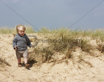 little boy on sand dunes