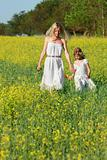mother and daughter in traditional clothes walking in yellow flo