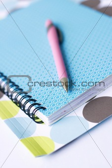 Brightly colored notebook, folder and pen.