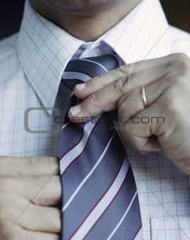 Business man adjusting his tie.