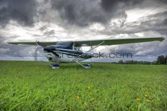 Aircraft on the field against thunderstorm clouds background