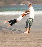 Father and son playing on a beach