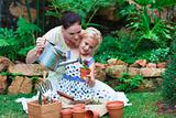 Young mother and daughter watering plants
