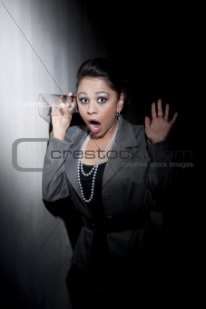 Pretty young Hispanic woman using glass to eavesdrop