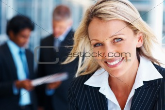 Smiling businesswoman with colleagues discussing in background