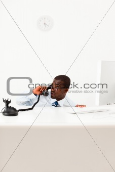 businessman hiding behind desk