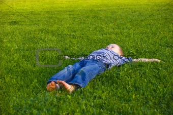 Boy lies on a grass