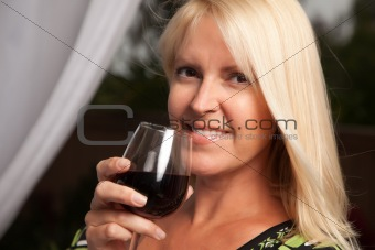 Beautiful blonde smiling woman at an evening social gathering tasting wine.