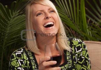 Beautiful blonde smiling woman at an evening social gathering tasting wine.