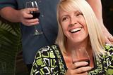 Wine Drinking Blonde Socializing with Man at an Evening Gathering.
