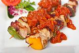shashlik on a plate with a tomato and salad leaf