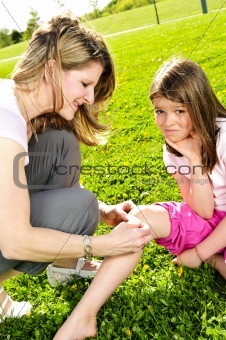 Mother putting bandage on child