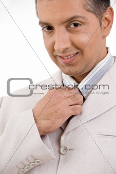 close view of smiling businessman holding tie