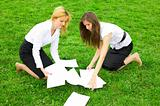 Two business women gather around on the grass paper
