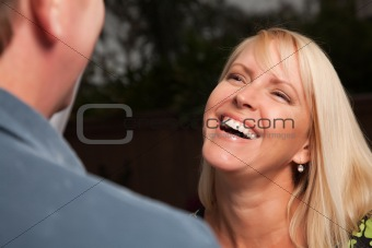 Attractive Blonde Woman Socializing with Man at an Evening Gathering.