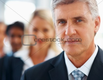 Portrait of a business man with his staff behind him
