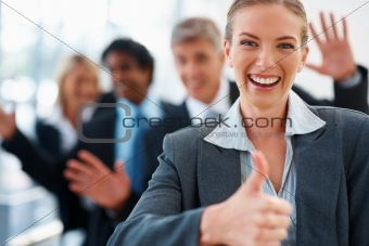 Happy business woman showing a success sign