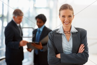 Confident business woman with her colleagues discussing in the background
