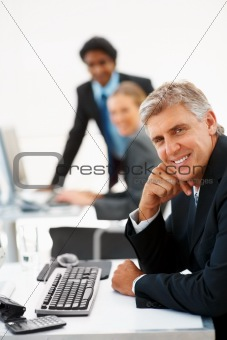 Mature business man at work with his associates working in the background