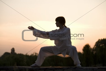 woman in white suit make's taiji chuan exercise