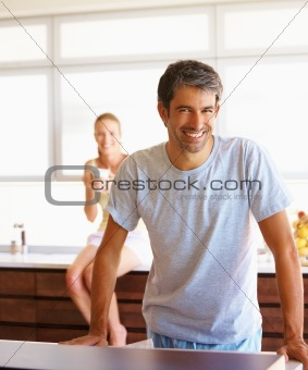Portrait of a smiling casual man standing in the kitchen