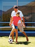 Father and daughter playing football