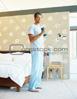 Mature man exercising in his bedroom with dumbells