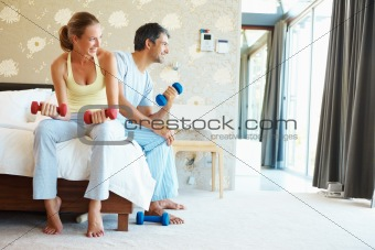 Happy couple exercising in bedroom with dumbells