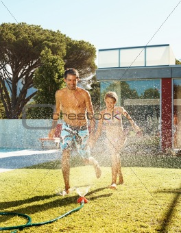 Cheerfu father and daughter running though a sprinkler