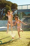 Cheerful girls running though a sprinkler