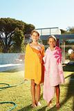 Portrait of two girls wrapped in towel in the backyard