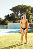 Young boy in swimwear standing at his backyard