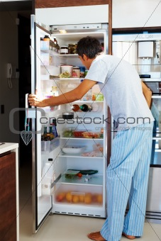 Man looking inside a fridge