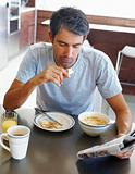 Man reading the newspaper while having breakfast
