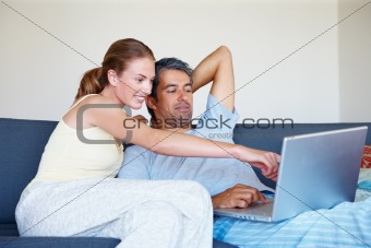 Happy mature couple working together on a laptop at home