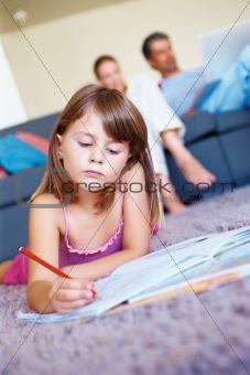 Cute girl studying while lying on the floor with her parents sitting on sofa in the background