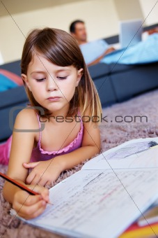 Cute young girl lying on the floor and studying