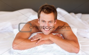 Attractive man smiling on bed