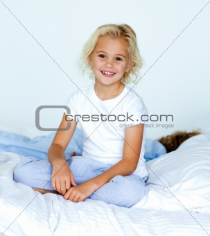 Little girl in bed smiling at the camera while her brother is sl