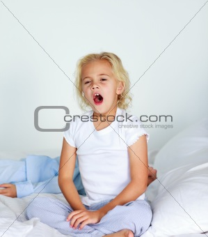Beautiful daughter yawning in bed