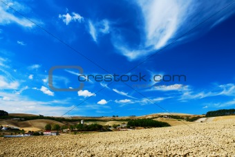 Pale blue and white sky over cultivated land