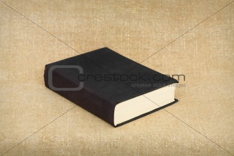 Old big black book on brown canvas background