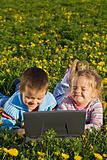Two kids outdoors having fun with a laptop