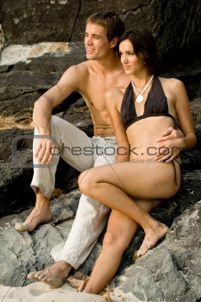 A young couple sitting together on the rocks