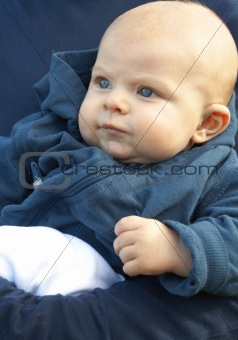 Small newborn baby in blue jacket